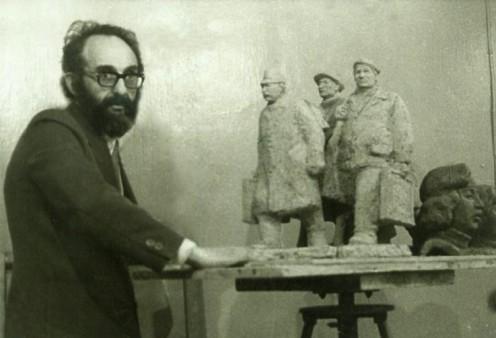 Лев опирается о столик со скульптурной композицией идущих художников